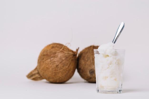 Vaso de aceite de coco con nueces de coco