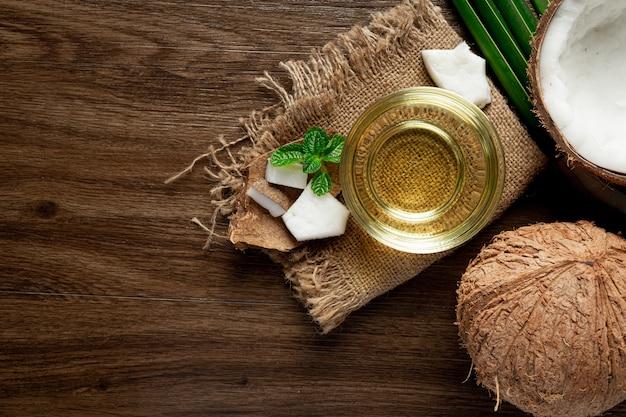 Vaso de aceite de coco puesto sobre un piso oscuro de madera