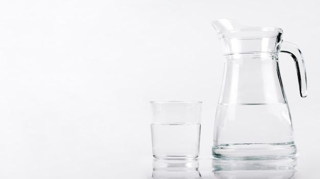 Vaso de agua al lado de jarra