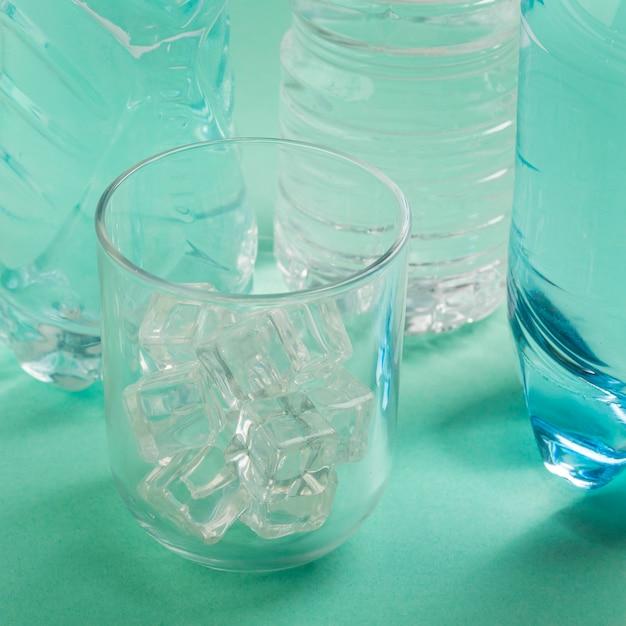 Vaso de agua y botellas de plástico. Foto gratis