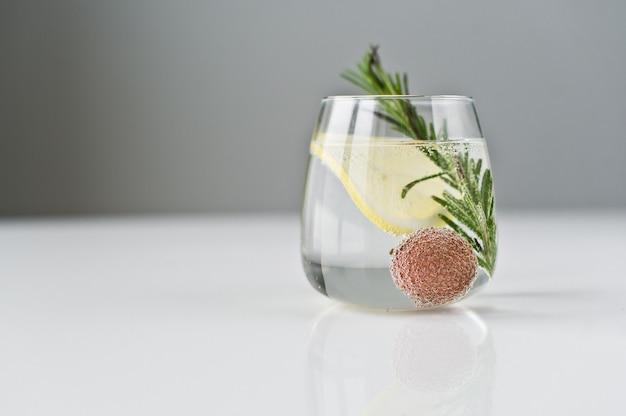 Vaso de agua clara con limón, romero, lichi.