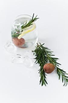 Vaso de agua clara con limón, romero.