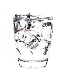 Vaso de agua con cubitos de hielo en la pared blanca