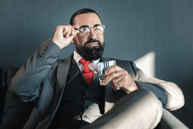 Vaso de agua. exitoso empresario con gafas sosteniendo un vaso de agua sentado en la habitación del hotel