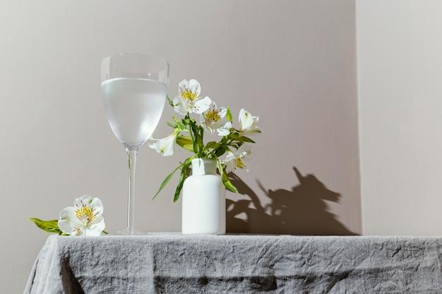 Vaso de agua y flores en la mesa