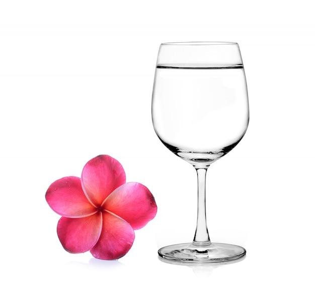 Vaso de agua y frangipani flor aislado fondo blanco.