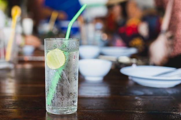 Vaso de agua fresca con gas con una rodaja de limón en la mesa
