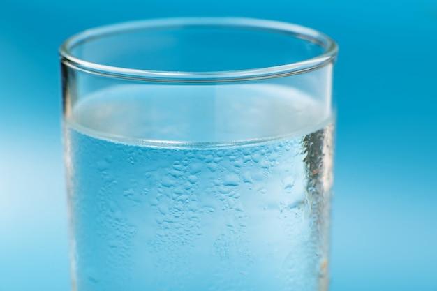 Vaso de agua fría pura sobre un fondo azul de cerca mojado.