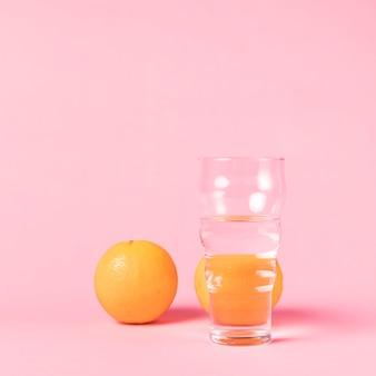 Vaso de agua y fruta de naranja