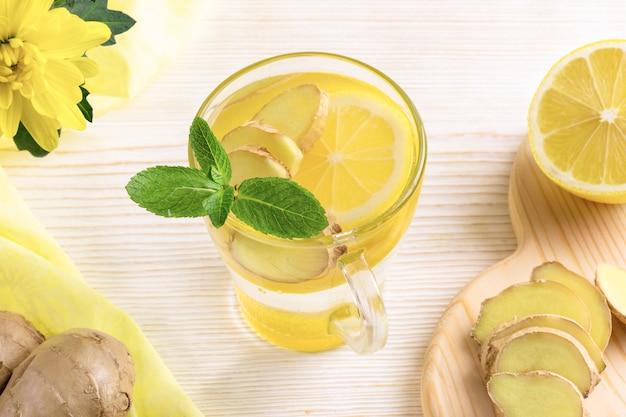 Vaso de agua, infundido con limón y jengibre en la mesa de madera clara.