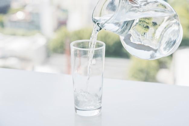 Vaso de agua jarra llenando