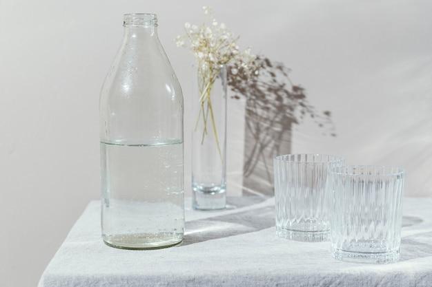 Vaso de agua y jarrón con flores.