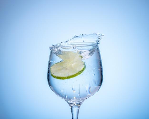 Vaso de agua con limón caído y salpicaduras sobre fondo degradado azul claro.