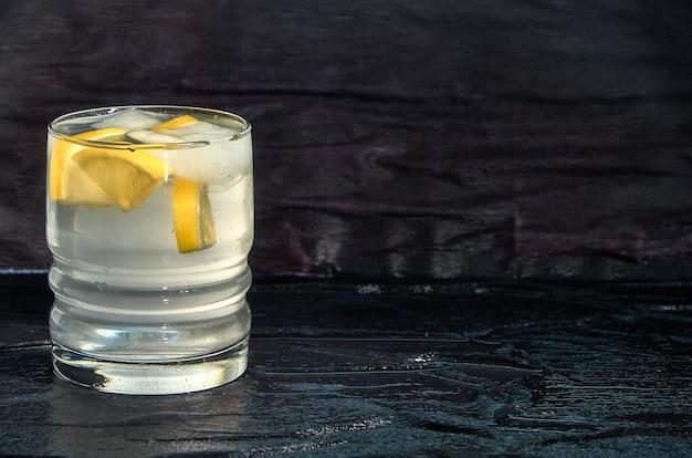 Un vaso de agua con limón y hielo.