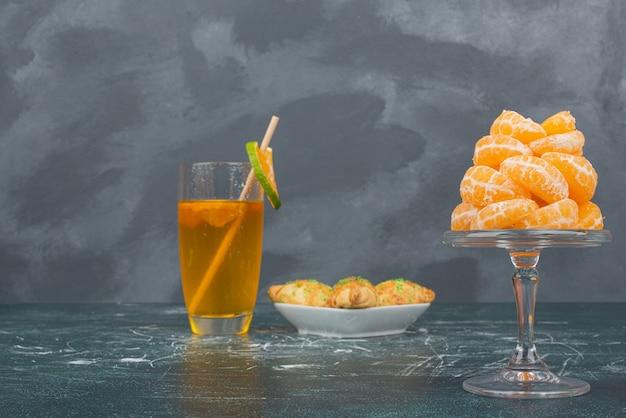 Vaso de agua de limón con plato de panadería dulce y rodajas de mandarina.