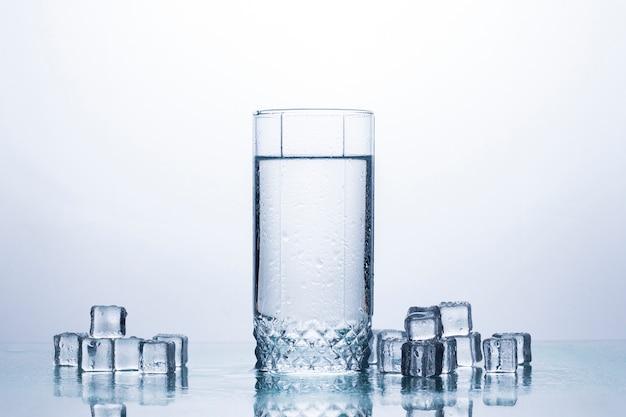 Un vaso de agua limpia y refrescante y cubitos de hielo. los