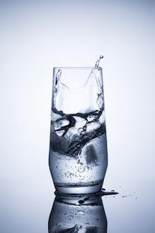 Vaso de agua mineral con gas con hielo en azul