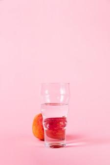 Vaso de agua y nectarina sobre fondo rosa