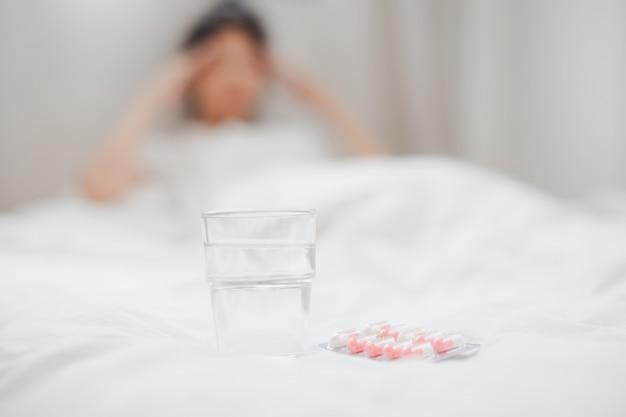 Un vaso de agua y la píldora en la cama con borrosa mujer enferma en el fondo.