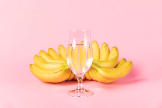Vaso de agua con plátanos en segundo plano.