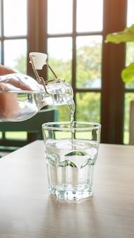 Un vaso de agua potable en una mesa de madera.