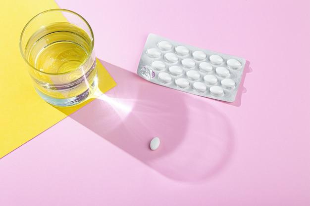 Vaso de agua de primer plano, blister con píldoras médicas blancas, tabletas para la prevención de virus, vitaminas, analgésicos en la pared rosa y amarilla, horizontal, espacio de copia, vista superior, luz solar