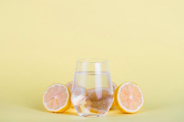 Vaso de agua rodeado de limones en rodajas