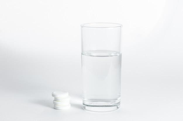Vaso de agua y tabletas efervescentes solubles.