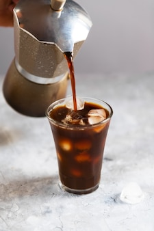 Vaso alto de café frío con hielo en la pared negra u oscura