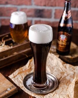 Vaso alto de cerveza negra con espuma