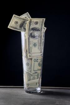 Vaso alto lleno de billetes de dólar sobre negro.
