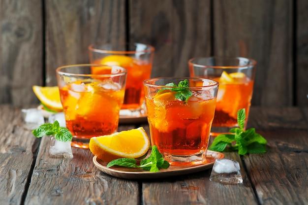 Vaso de aperol con hielo, naranja y menta.