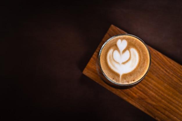Un vaso de arte latte en placa de madera sobre tabla de madera
