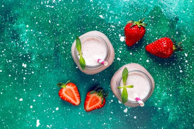 Vaso de batido de fresa fresco, batido y fresas frescas