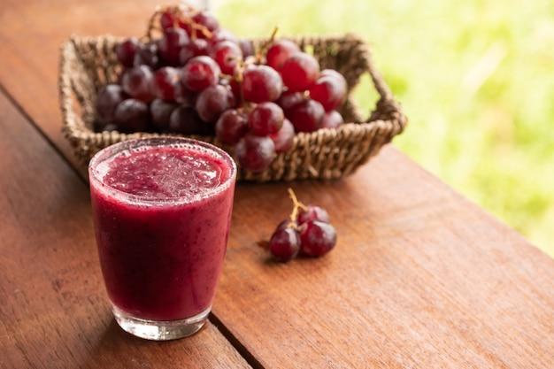 Vaso de batido de jugo de uva en la mesa de madera