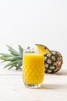 Vaso de batido de piña fresca sobre mesa de madera - bebida saludable