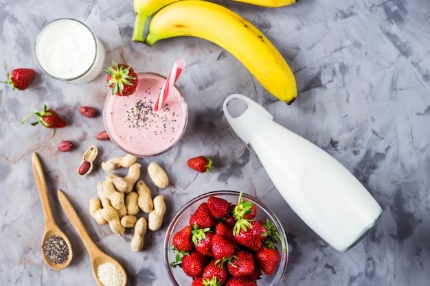 Un vaso de batido de plátano y fresa entre los ingredientes para su cocción.