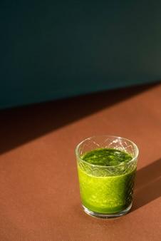 Vaso de batido verde delicioso de alto ángulo