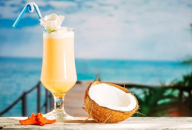 Vaso de bebida amarilla suave con estrella de mar naranja y coco agrietado