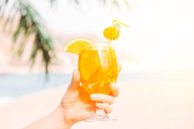 Vaso de bebida aromática de naranja en la mano.