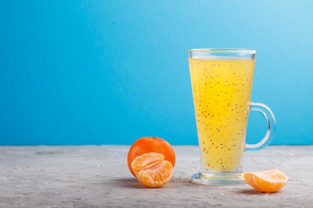 Vaso de bebida de color naranja mandarina con semillas de albahaca. vista lateral