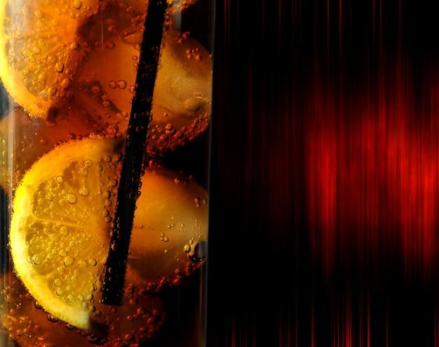 Vaso con bebida coque hielo y limones.