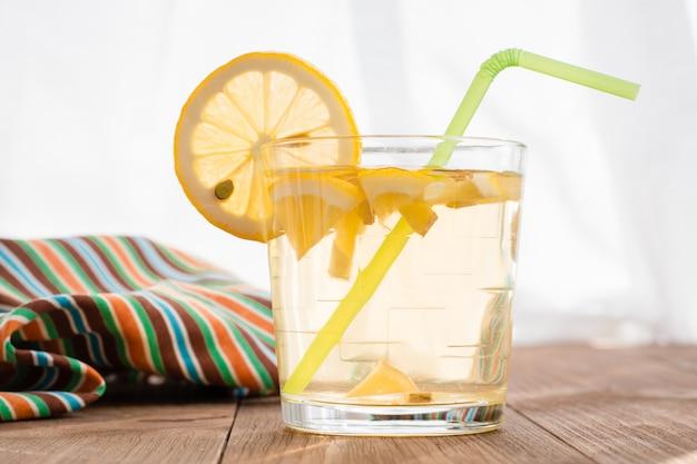 Un vaso con una bebida fría de limón y jengibre