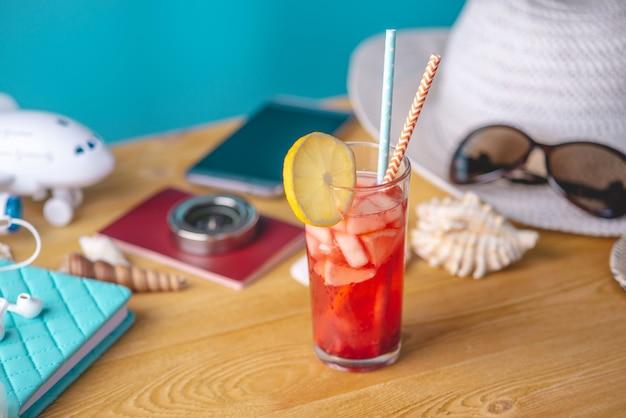 Vaso de bebida de limonada roja con limón y fruta y paja sobre la mesa