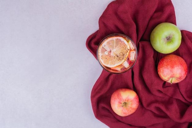 Un vaso de bebida con manzanas rojas y verdes.