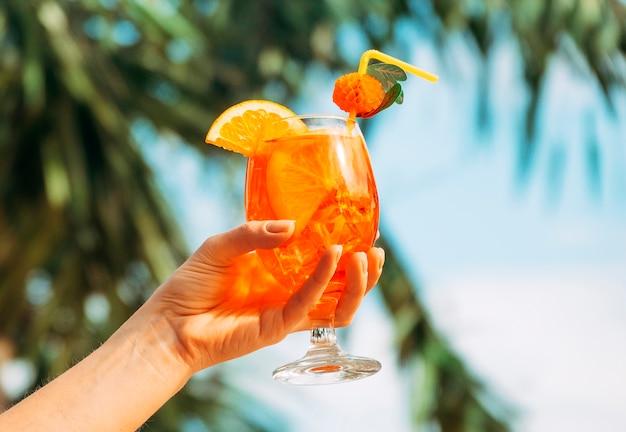Vaso de bebida de naranja brillante fresco en la mano