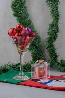 Un vaso de bolas de navidad con calcetín en pared gris.