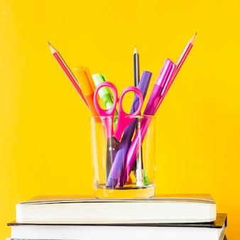 Un vaso con bolígrafos, lápices y tijeras sobre una pila de libros para entrenar