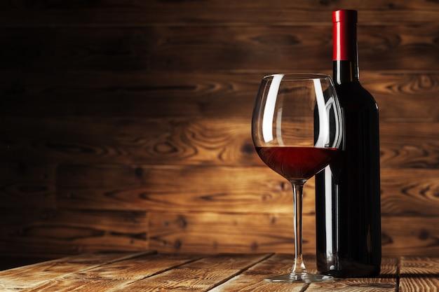 Vaso y botella con delicioso vino tinto en mesa contra madera