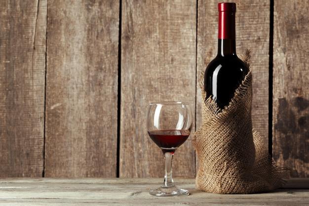 Vaso y botella con delicioso vino tinto en la mesa contra la pared de madera